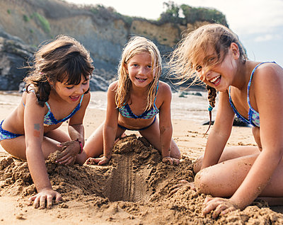 Spain, Colunga, three girls playing on the beach - p300m1188456 by Marco Govel