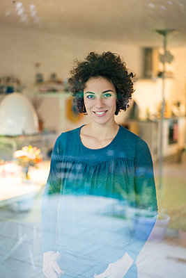 Portrait of smiling woman standing behind window at home - p300m2080522 von Joseffson