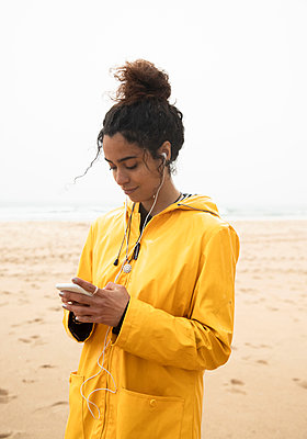 Smiling woman using mobile phone while standing at beach - p300m2256065 by Sebastian Kanzler