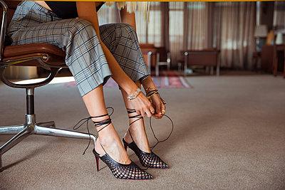 Junge Frau bindet sich die High Heels zu - p432m2027612 von mia takahara