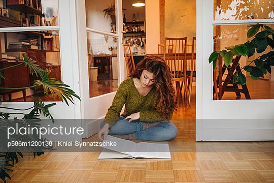 Junge Frau durchblättert ein Buch  - p586m1200138 von Kniel Synnatzschke