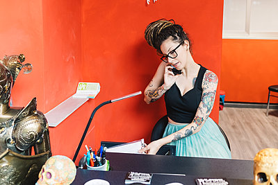 Tattooist talking on mobile phone in parlour - p429m2032614 by Eugenio Marongiu