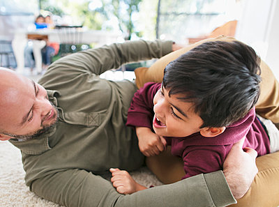 Playful father and son on floor - p1023m2074020 by Robert Daly