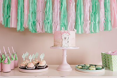 Llama birthday cake on a green and pink themed dessert table - p1166m2106589 by Cavan Images