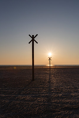 Denmark, Romo, Silhouettes of distance markers on coastal beach at sunset - p300m2180015 by Anke Scheibe