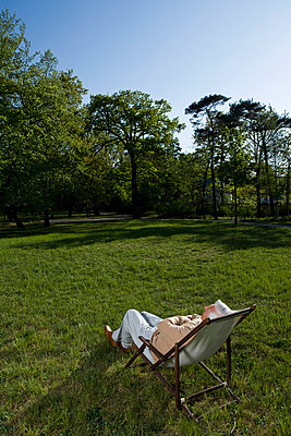 A senior man reclining in a lounge chair on a lawn - p3019722f by Paul Hudson