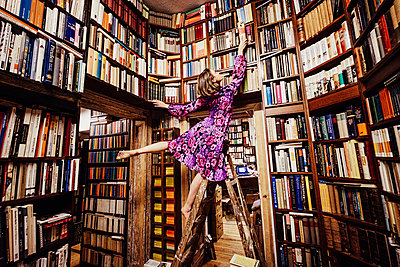 Carefree woman on ladder reaching for book in library - p301m2070920 by Sven Hagolani