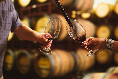 Caucasian couple tasting wine in cellar - p555m1415546 by Inti St Clair