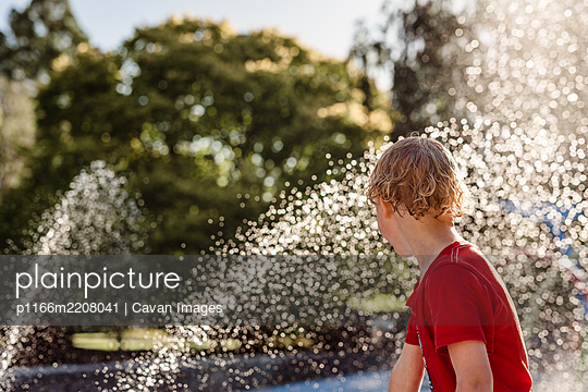 Child playing in with water in a park in New Zealand - p1166m2208041 by Cavan Images