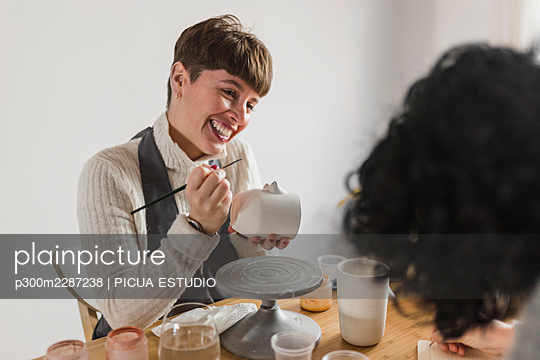 Smiling female painter with paintbrush and mug looking at colleague in workshop - p300m2287238 by PICUA ESTUDIO
