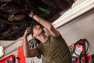 Low angle view of mechanic repairing car in auto repair shop - p1166m2105712 by Cavan Images