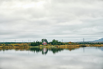 Rural landscape of red house on green lake shore - p1166m2157257 by Cavan Images