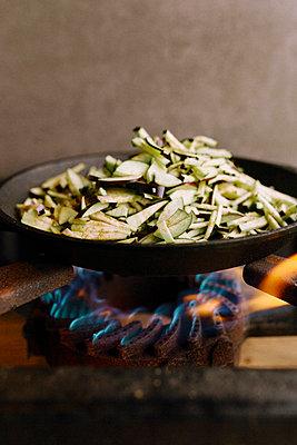 Aubergine in gusseisener Pfanne wird zum veganen Gericht auf Gasflamme gekocht  - p1497m2149570 von Sascha Jacoby