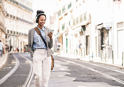 Smiling young woman with headphones and mobile phone in the city on the go, Lisbon, Portugal - p300m2144573 by Uwe Umstätter