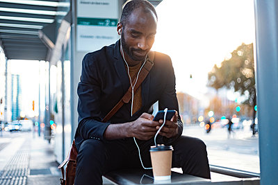 Young businessman sitting at tram stop in the evening using earphones and smartphone - p300m2160650 von Josep Suria