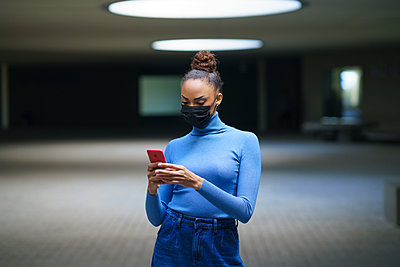 Young woman wearing protective face mask using mobile phone while standing in illuminated parking garage - p300m2266969 by Javier Sánchez Mingorance