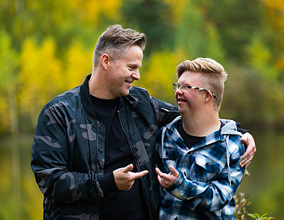 A young man with Down Syndrome and his father enjoying each other's company and giving each other funny hand gestures in a city park on a warm fall evening: Edmonton, Alberta, Canada - p442m2154376 by LJM Photo