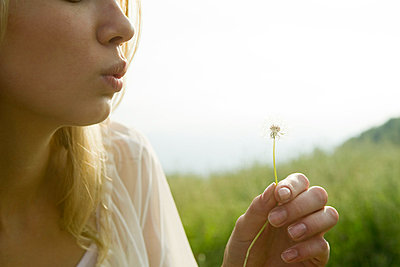 Young woman blowing dandelion seedhead - p6244231f by Laurence Mouton