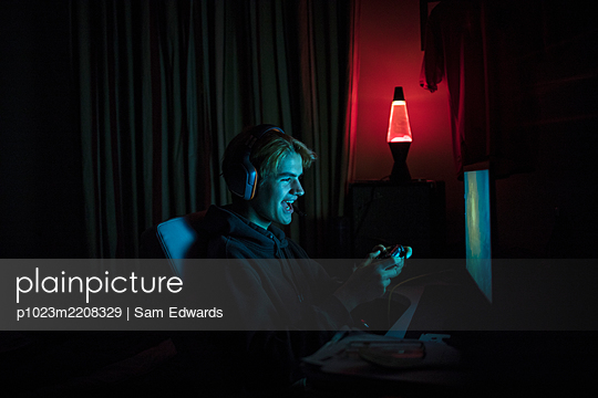 Smiling teenage boy playing video game at computer in dark bedroom - p1023m2208329 by Sam Edwards