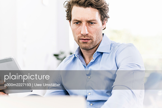 Man concentrating while using digital tablet sitting in office - p300m2227193 by Uwe Umstätter