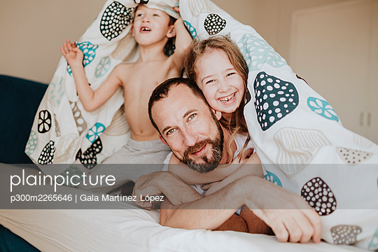 Cheerful daughter with father while brother looking away under blanket on bed at home - p300m2265646 by Gala Martínez López