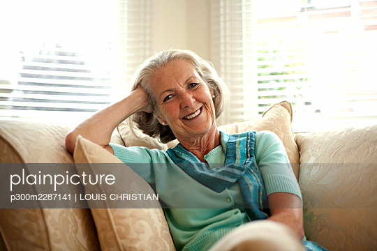 Smiling senior woman with head in hand sitting on sofa at home - p300m2287141 by LOUIS CHRISTIAN