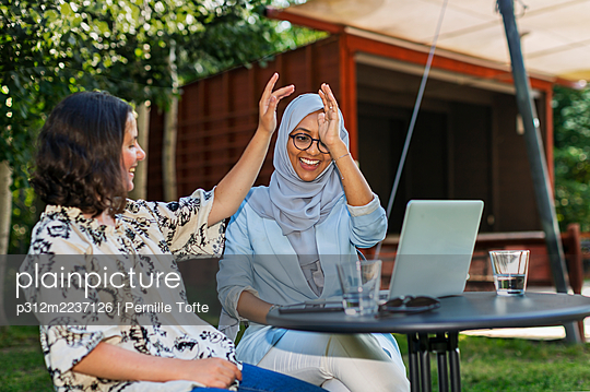 Female friends giving high five to each other - p312m2237126 by Pernille Tofte