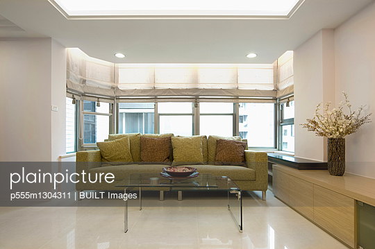 Green sofa and glass coffee table in modern living room - p555m1304311 by BUILT Images