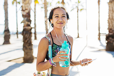 Portrait of happy sporty woman holding water bottle on footpath during summer - p1166m1163552 by Cavan Images