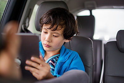 A boy sits in a carseat on a car trip watching a tablet - p1166m2165929 by Cavan Images