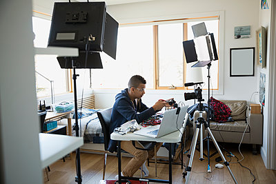 Boy videotaping electronics assembly bedroom - p1192m1129551f by Hero Images