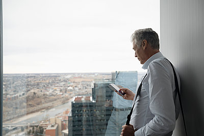 Senior businessman using smart phone at urban office window - p1192m1583512 by Hero Images
