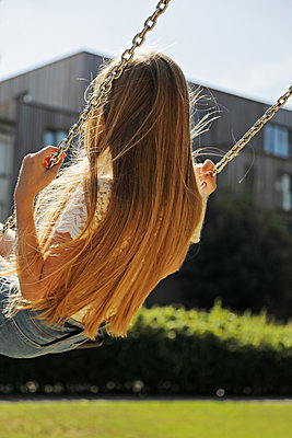 Teenage girl on a swing  - p1540m2122845 by Marie Tercafs