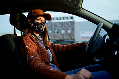 Young woman with cap and face mask driving car in city - p300m2221074 by Kiko Jimenez