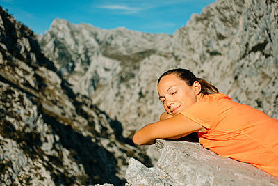 Woman with eyes closed relaxing on rock at Cares Trail in Picos De Europe National Park, Asturias, Spain - p300m2250821 by David Molina Grande