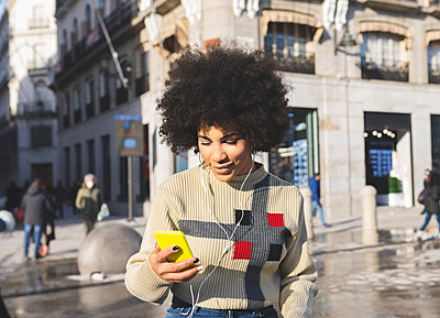 Smiling woman using mobile phone while standing in city - p300m2252584 by Jose Carlos Ichiro