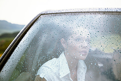Womans face behind car windscreen in rain dreaming - p4020432 by Ramesh Amruth