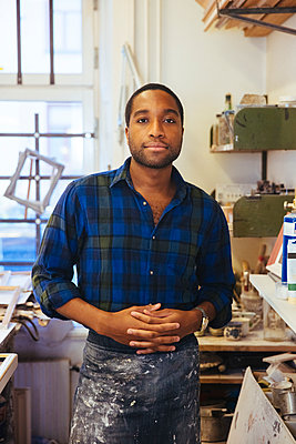 Portrait of young male framing artist standing with hands clasped at workshop - p426m2089080 by Maskot