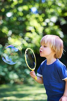 Boy blowing oversized bubble in backyard - p42916174f by Ghislain & Marie David de Lossy