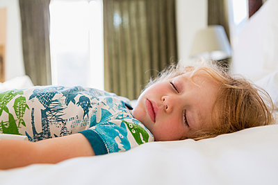 Caucasian boy sleeping on bed - p555m1410690 by Marc Romanelli
