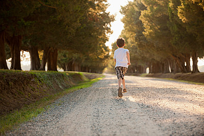 Caucasian boy running on dirt road - p555m1478562 by Mark Edward Atkinson/Tracey Lee