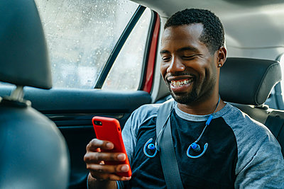 Smiling Black man texting on cell phone in car - p555m1532373 by Inti St Clair