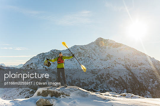 Man standing on mountain summit holding paddle and inflatable boat - p1166m2255911 by Cavan Images