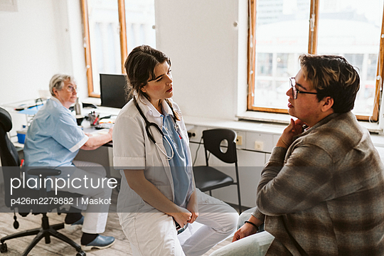 Female medical expert discussing with male patient while senior nurse sitting at desk - p426m2279882 by Maskot