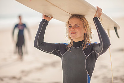 Young woman carrying surfboard on her head on the beach - p300m1176010 by zerocreatives