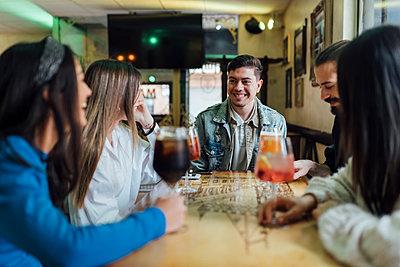 Happy friends having drinks in restaurant - p300m2242816 by Ezequiel Giménez