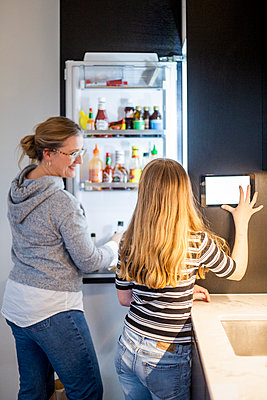Daughter using digital tablet while mother looking standing by refrigerator at smart home - p426m2195144 by Maskot