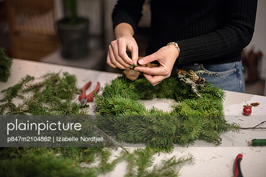 Woman's Hand Preparing Wreath During Christmas   - p847m2104862 by Izabelle Nordfjell