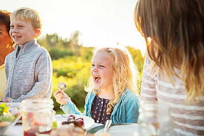 Girl enjoying with family on picnic table - p1166m1095846f by Cavan Images