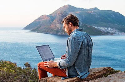 Side view of man using laptop on hill against mountain and sea - p1166m1461695 by Cavan Images